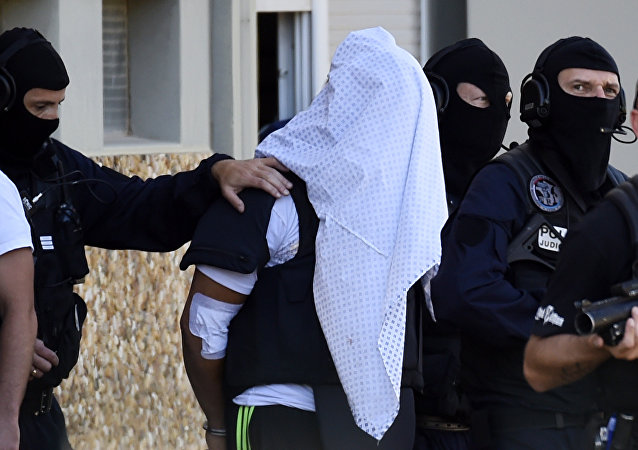 French police escort Yassin Salhi (C), a man suspected of decapitating his boss in an attack on a gas factory, as they leave his flat in Saint-Priest on June 28, 2015