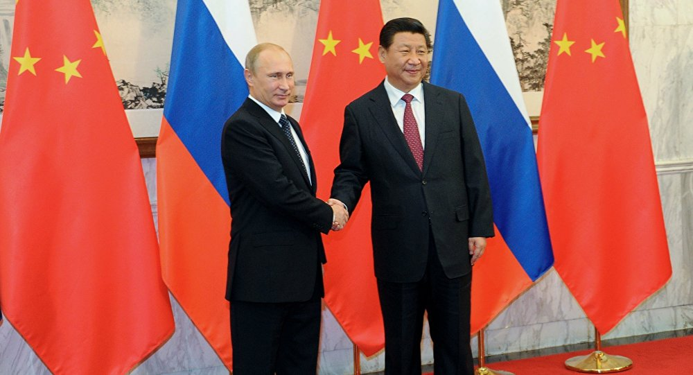 Russian President Vladimir Putin, left, shakes hands with Chinese President Xi Jinping prior to the Asia-Pacific Economic Cooperation (APEC) forum in Beijing