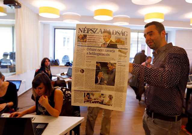 Journalists of the leftist newspaper Nepszabadsag, which was unexpectedly shut down on Saturday amid cries of a crackdown by right-wing Prime Minister Viktor Orban's government, paste a copy of the last issue onto the wall of a temporary newsroom in Budapest, Hungary, October 10, 2016