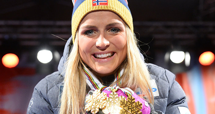 This file photo taken on February 28, 2015 shows Norway's Therese Johaug celebrating with her three gold medals during the medals ceremony of the women's cross country 30 km mass start classic style competition of the 2015 FIS Nordic World Ski Championships in Falun, Sweden.
