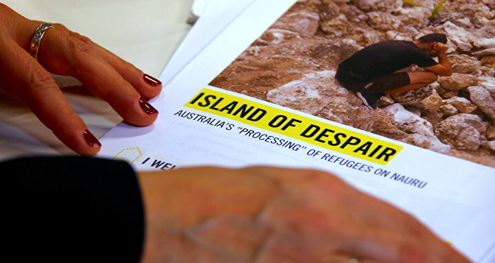 Anna Neistat, Senior Director for Research with Amnesty International, talks to journalists as she holds a copy of a report she co-authored titled 'Island of Despair - Australia's Processing of Refugees on Nauru' in Sydney, Australia, October 17, 2016