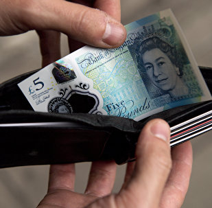 In this posed photograph a person is pictured holding a wallet containing a £5 (five pound) note in London on October 7, 2016.