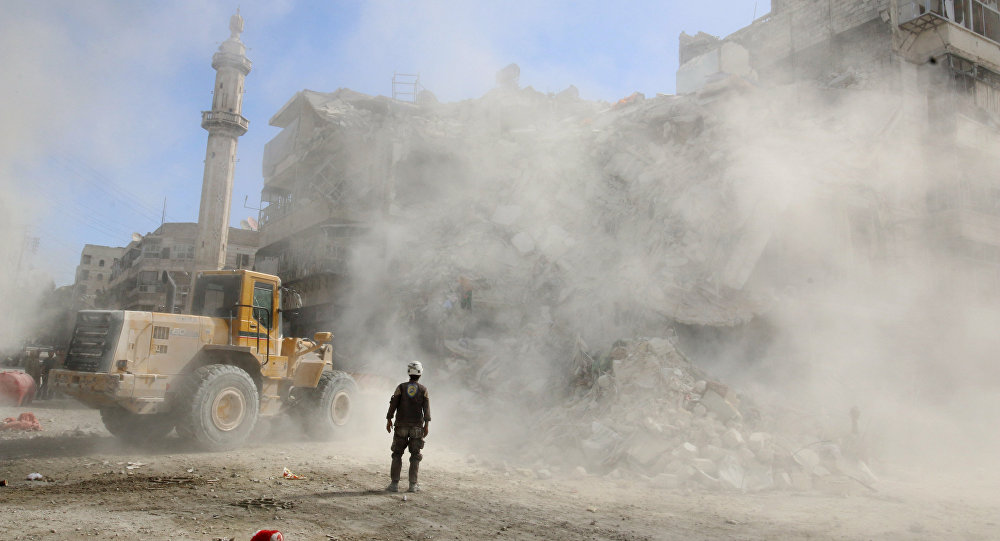 A Civil Defence member stands as a front loader removes debris after an air strike, Aleppo, Syria