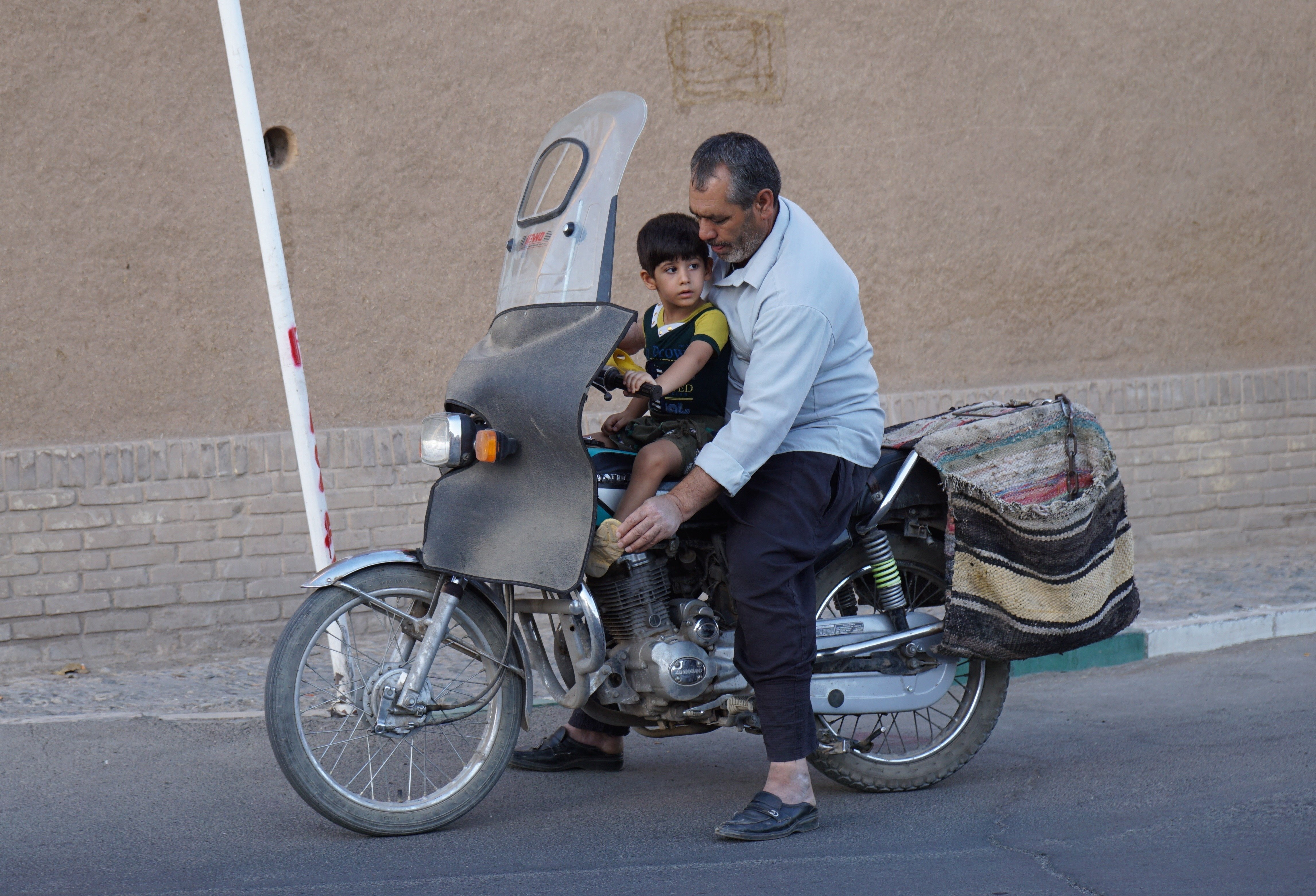 Iranian man drives his son on a bike