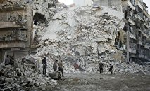 Members of the Syrian Civil Defence, known as the White Helmets, search for victims amid the rubble of a destroyed building following reported air strikes in the rebel-held Qatarji neighbourhood of the northern city of Aleppo, on October 17, 2016