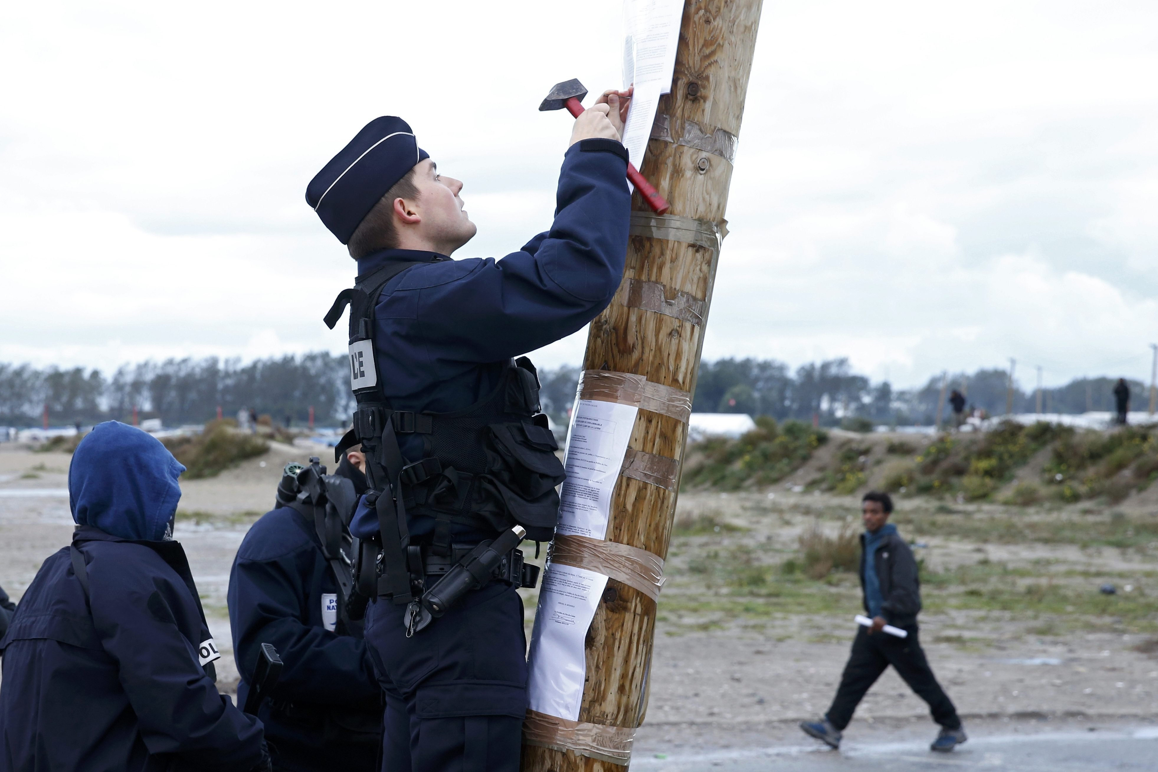 A French policeman posts the official document that announces the dismantling of the makeshift camp called the Jungle, as a migrant walks past in Calais, France, October 21, 2016