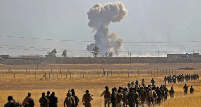 Smoke billows from an area near the Iraqi town of Nawaran, some 10km north east of Mosul, as Iraqi Kurdish Peshmerga fighters march down a dirt road on October 20, 2016, during the ongoing operation to retake the city from the Islamic State (IS) group