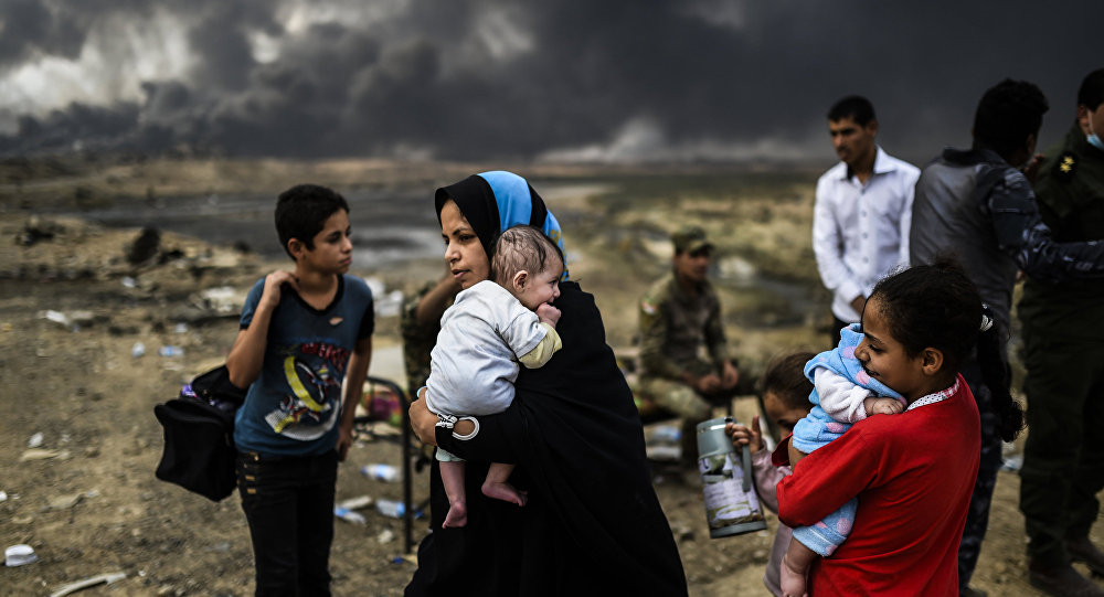 Iraqi families, who were displaced by the ongoing operation by Iraqi forces against jihadistds of the Islamic State group to retake the city of Mosul, are seen gathering on an area near Qayyarah on October 24, 2016