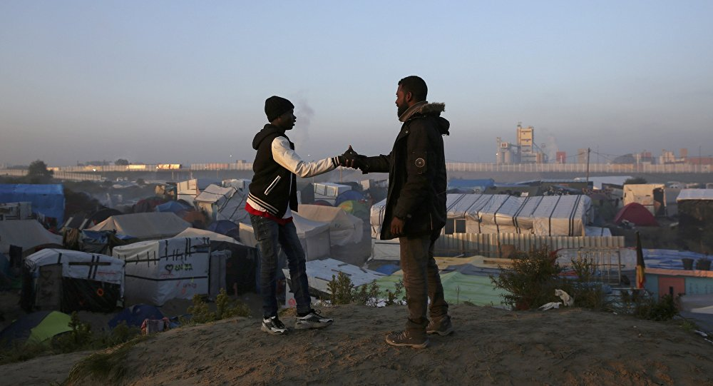 Migrants shake hands as they stand on a high point near tents and makeshift shelters on the second day of their evacuation and transfer to reception centers in France, during the dismantlement of the camp called the Jungle in Calais, France, October 25, 2016