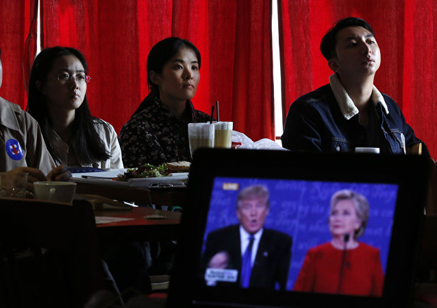 Chinese students watch live broadcasting of the U.S. presidential debate between Democratic presidential nominee Hillary Clinton and Republican presidential nominee Donald Trump, at a cafe in Beijing, Tuesday, Sept. 27, 2016