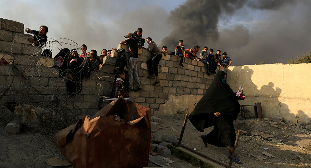 A newly displaced woman runs after she jumped over a back wall and rushed to grab humanitarian packages, as smoke rises from a burning oil refinery at a processing centre in Qayyara, south of Mosul, Iraq October 25, 2016