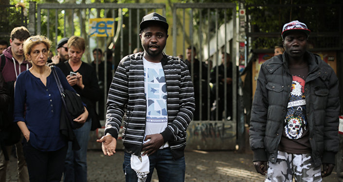 Sudanese refugees, who said their names are Adam, center, and Anour, right, speak to media in front of the entrance of the occupied Gerhart Hauptmann School in Berlin, Germany, Friday, June 27, 2014