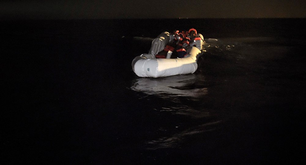 Refugees and migrants wait to be rescued from their sinking rubber boat some eight nautical miles off Libya's Mediterranean coastline on October 12, 2016