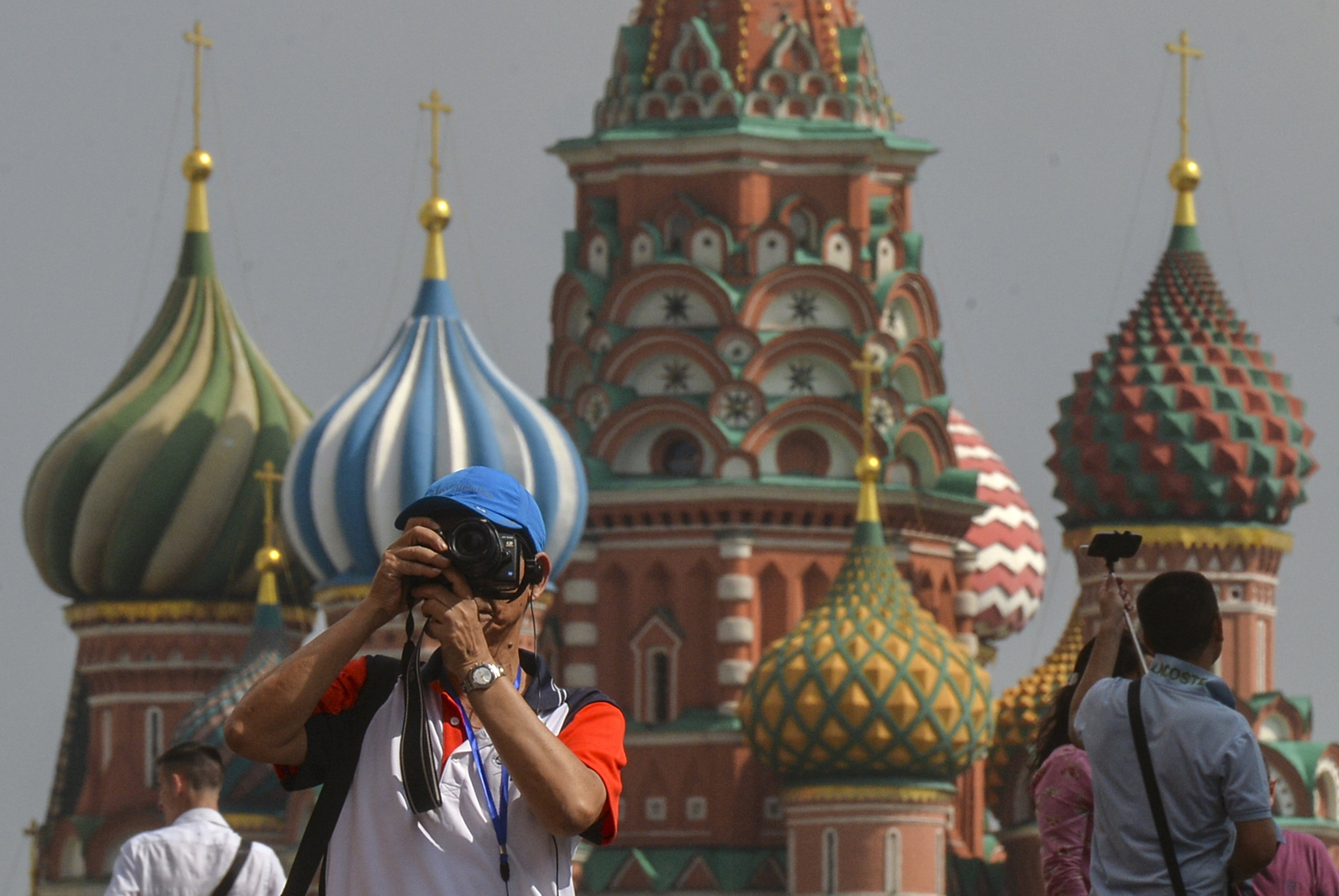 A tourist takes pictures on Red Square, Moscow.Experts predict influx of foreign tourists to Russia
