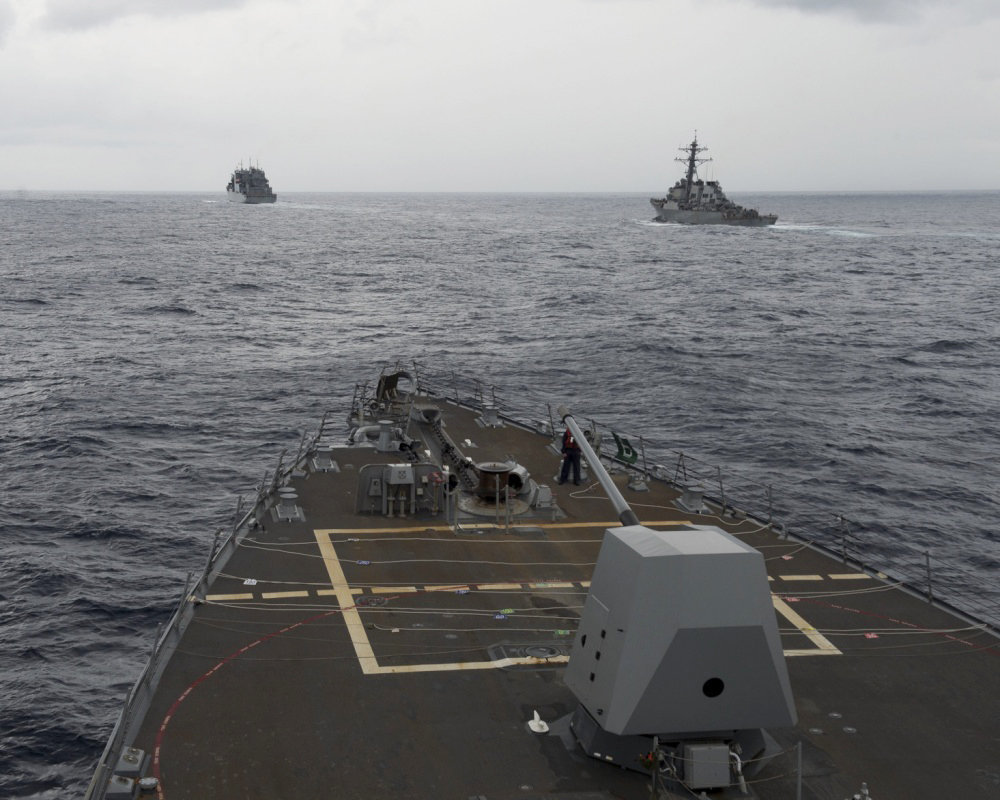 the guided missile destroyer USS Decatur, right, pulling into position behind the Military Sealift Command USNS Matthew Perry, during a replenishment-at-sea, seen from the bridge of the guided-missile destroyer USS Spruance, in the South China Sea.