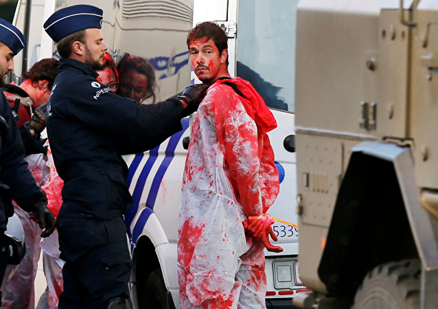 A demonstrator with red paint is detained by police officers during a protest against the Comprehensive Economic and Trade Agreement (CETA), a EU-Canada free trade agreement, outside the European Council in Brussels, Belgium, October 30, 2016.