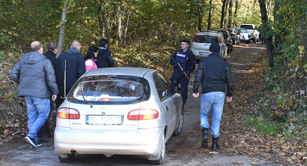 Police officers and forensic scientists examine the area of Jajincii where the weapons were discovered