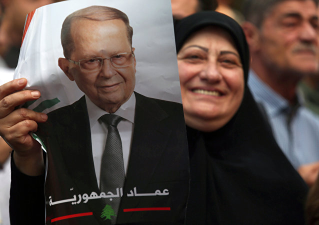 A woman carries a picture of newly elected Lebanese President Michel Aoun in the Haret Hreik area, southern suburbs of Beirut, Lebanon October 31, 2016
