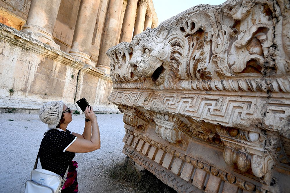 A visitor takes pictures of a bas-relief with heads of lions from the roof of the Temple of Jupiter in a temple complex of Baalbek, Lebanon