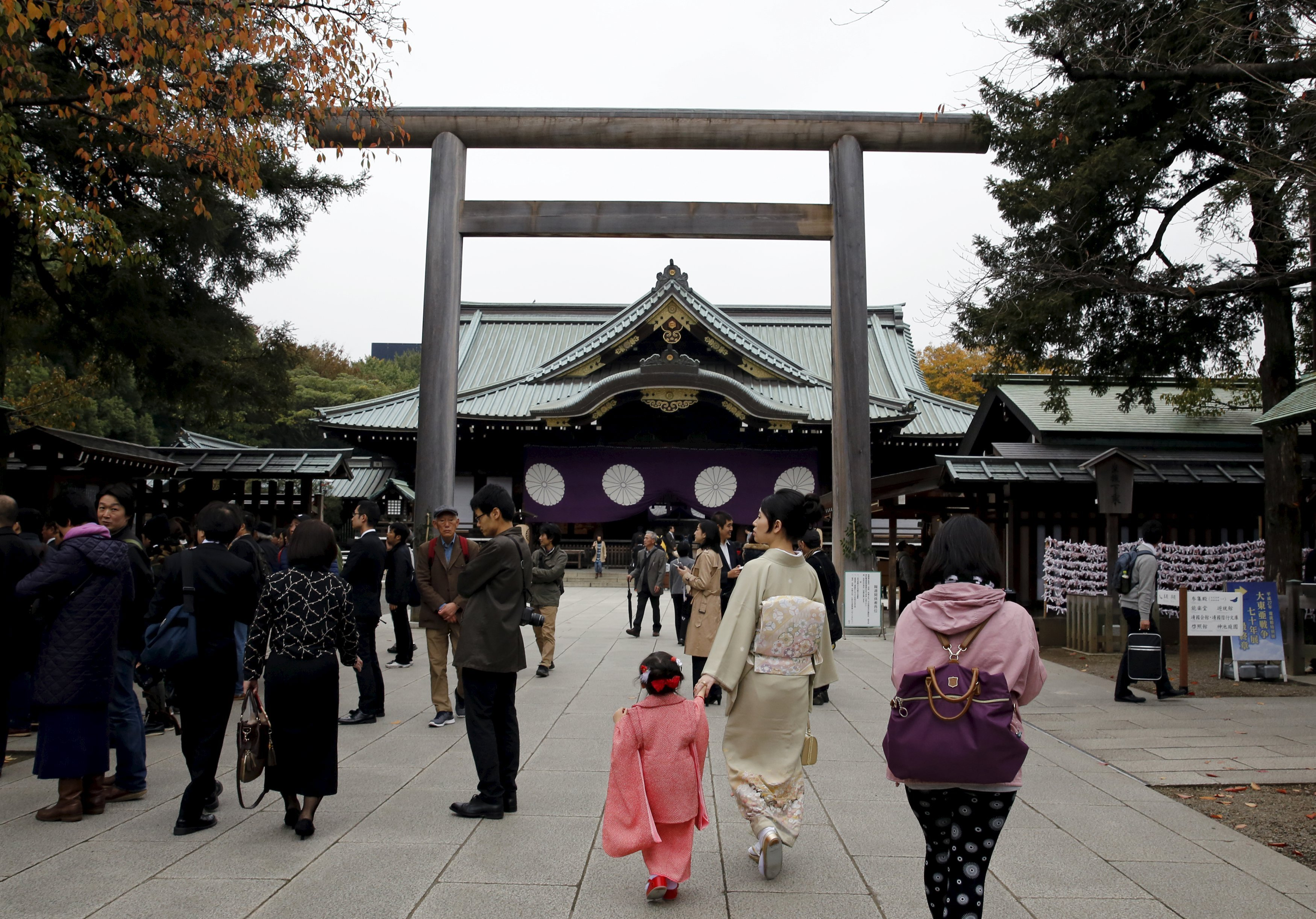 People walk near the main shrine after a blast at the precinct of the Yasukuni shrine in Tokyo, Japan, November 23, 2015