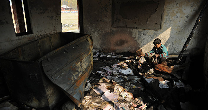 A Kashmiri student looks at damaged property at a partially burnt government high school in Goripora, on the outskirts of Srinagar on November 2, 2016