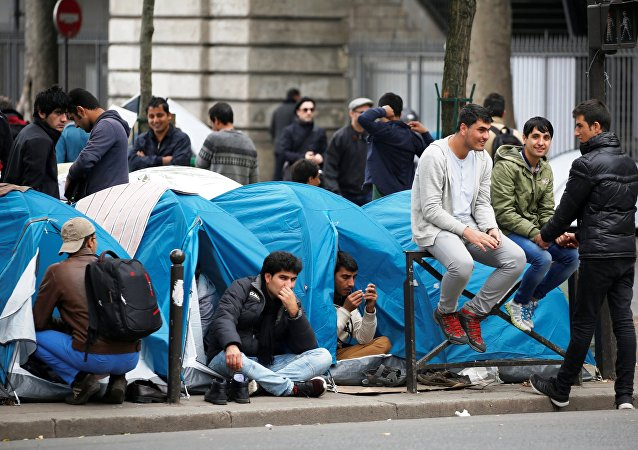 Migrants sit in their tents at a makeshift migrant camp on a street near the metro stations of Jaures and Stalingrad in Paris, France, 28 October 2016.
