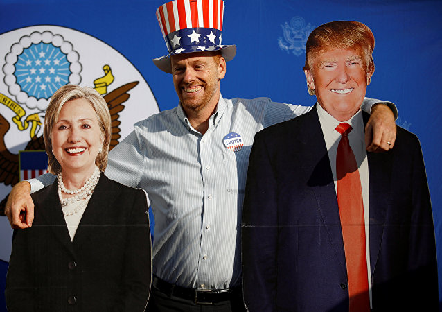 A man poses for a picture with the cardboard cutouts of US presidential nominees Hillary Clinton (L) and Donald Trump, at an election event hosted at the US ambassador's residence in Kathmandu, Nepal November 9, 2016.