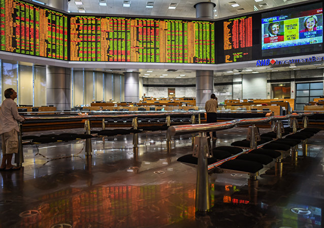 Traders monitor electronic boards showing stock movements during the final day of the US presidential election at a private stock exchange in Kuala Lumpur on November 9, 2016