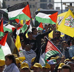 Palestinians wave their national flag and Fatah party flags as they take part in a rally marking the 12th anniversary of the death of late Palestinian leader Yasser Arafat (portrait background) in the West Bank city of Ramallah on November 10, 2016