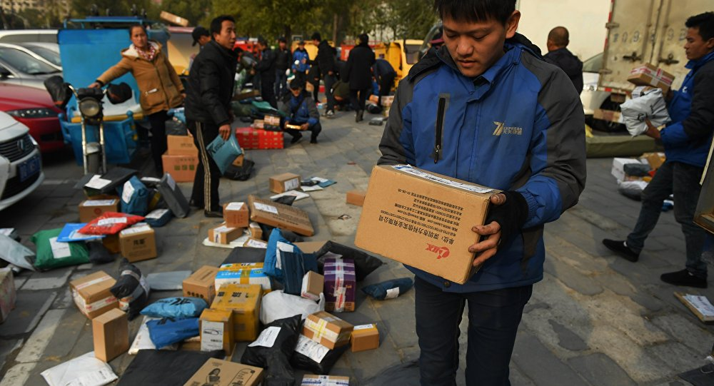 Delivery drivers sort packages for delivery at a sorting center during the 'Double Eleven' Online Shopping Festival day in Beijing on November 11, 2016