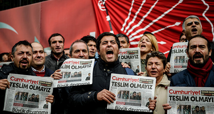 Protesters hold copies of the latest edition of the the Turkish daily newspaper Cumhuriyet as they shout slogans during a demonstration outside the newspaper's headquarters in Istanbul on November 1,2016 a day after its editor in chief was detained by police.