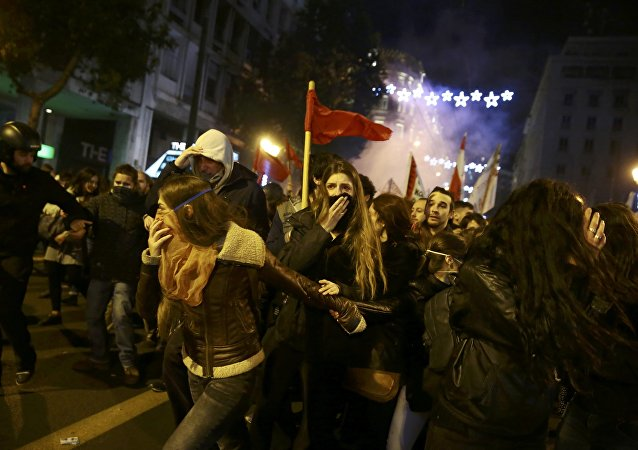 Protesters run away from teargas as they clash with riot police during a demonstration against the visit of U.S President Barack Obama, in Athens, Greece