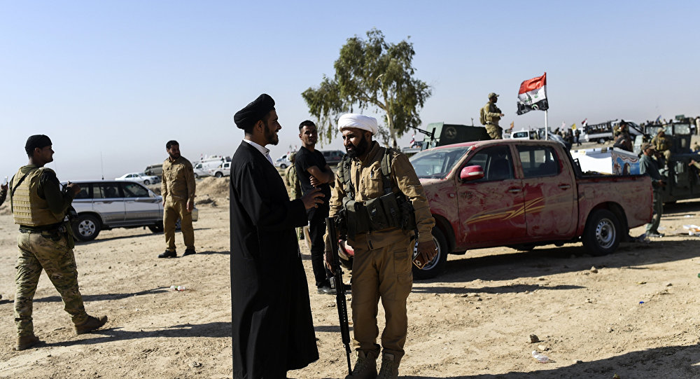 Members of Al-Hashd al-Shaabi faction talk on October 21, 2016, near the village of Tall al-Tibah, some 30 kilometres south of Mosul, during an operation to retake the main hub city from the Islamic State (IS) group jihadists
