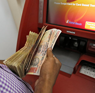 A customer deposits 1000 and 500 Indian rupee banknotes in a cash deposit machine at bank in Mumbai, India, November 8, 2016