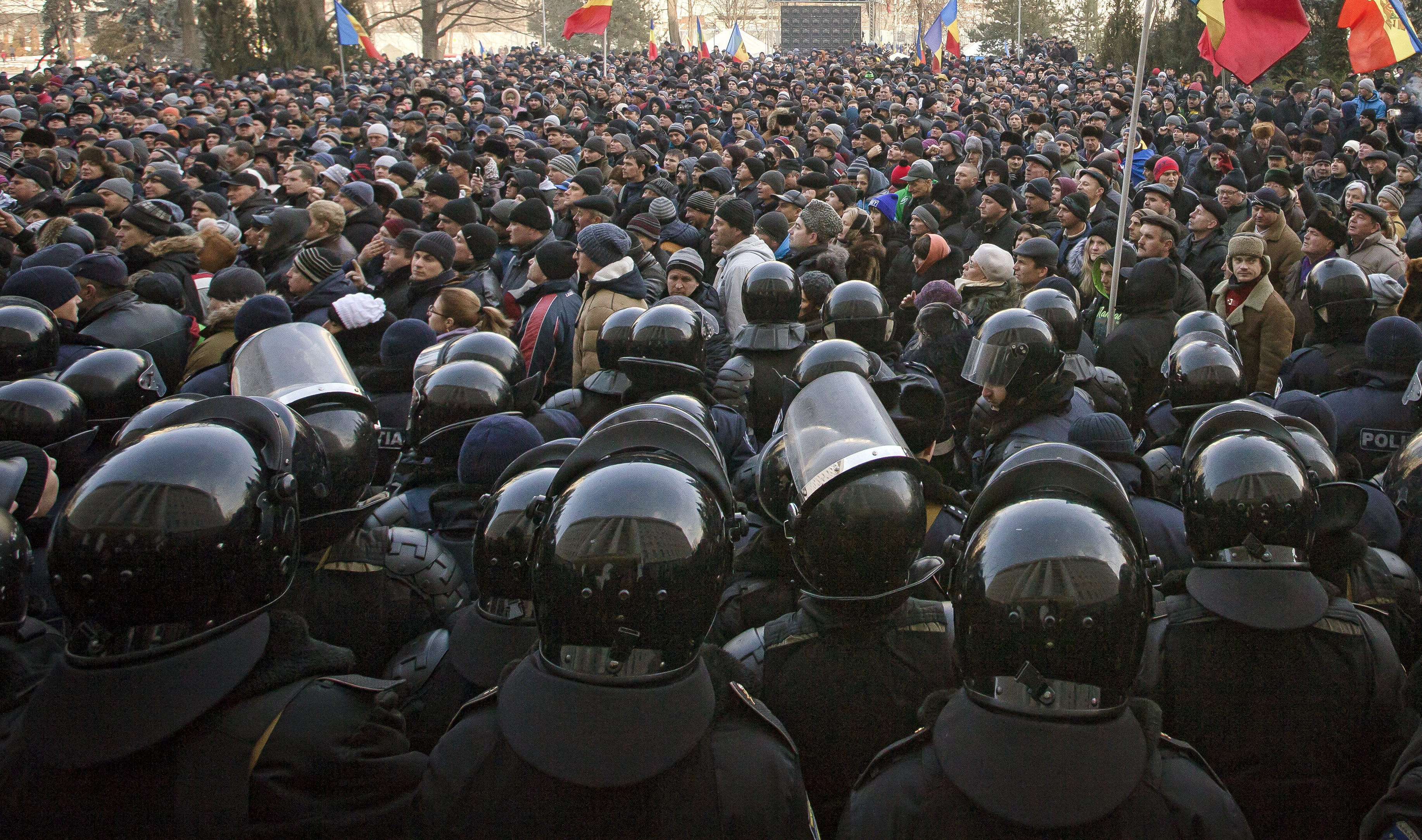 Riot police officers stand in line in front of protesters, some wanting closer links to Russia, others demanding a crackdown on corruption, outside the parliament in Chisinau, Moldova, Thursday, Jan. 21, 2016. The country has faced regular protests since early 2015.