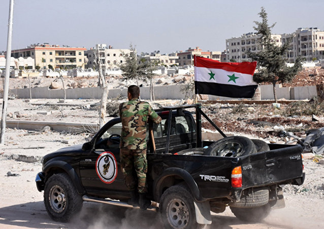 Members of Syrian pro-government forces drive their pick-up in the village of Minyan, west of Aleppo, after they retook the area from rebel fighters on November 12, 2016