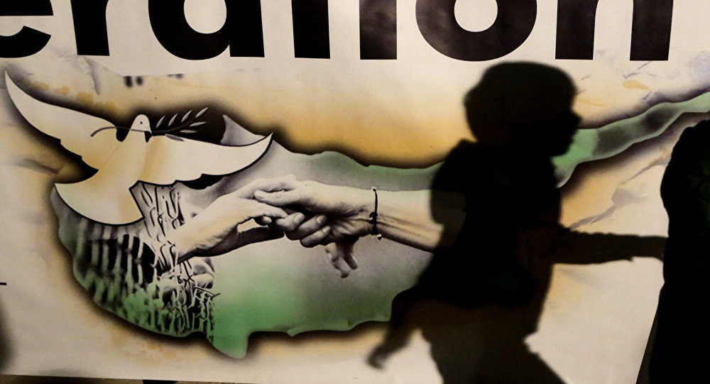 A shadow of a boy is seen on a banner showing the Cyprus island with two hands and a pigeon during a peace rally to support the peace talks inside the UN buffer zone Green Line, in the divided capital Nicosia in the eastern Mediterranean island of Cyprus, Monday, Nov. 21, 2016. Hundreds of Greek and Turkish Cypriots are demonstrating for peace as the ethnically divided island's rival leaders continue complex reunification talks at a Swiss resort.