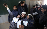 Members of the Syrian Civil Defence, known as the White Helmets, take a selfie with their certificates after taking part in a training session in the rebel-held eastern Ghouta area, east of the capital Damascus, on November 22, 2016