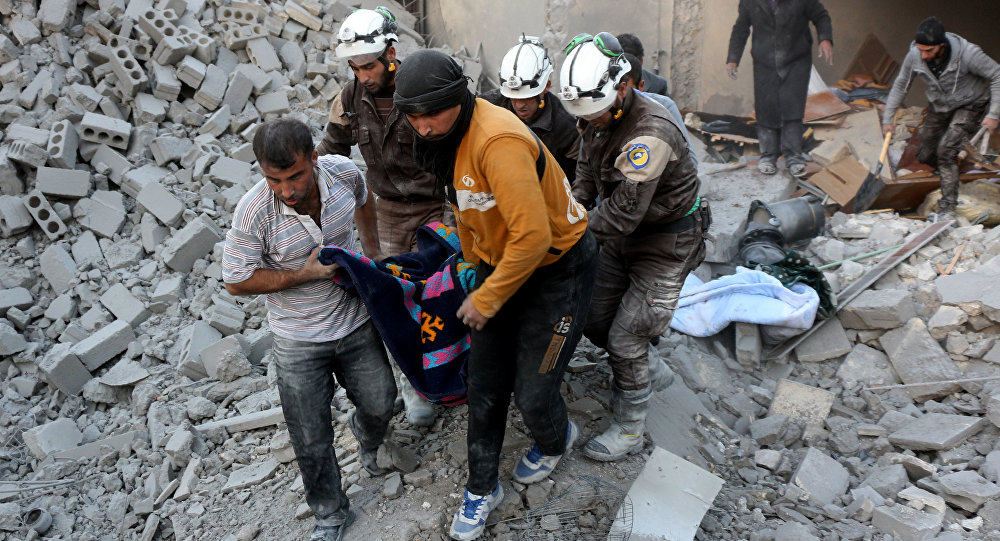 Syrian civil defence volunteers, known as the White Helmets, evacuate a victim from the rubble of a building following reported airstrikes on Aleppo's rebel-held district of al-Hamra on November 20, 2016