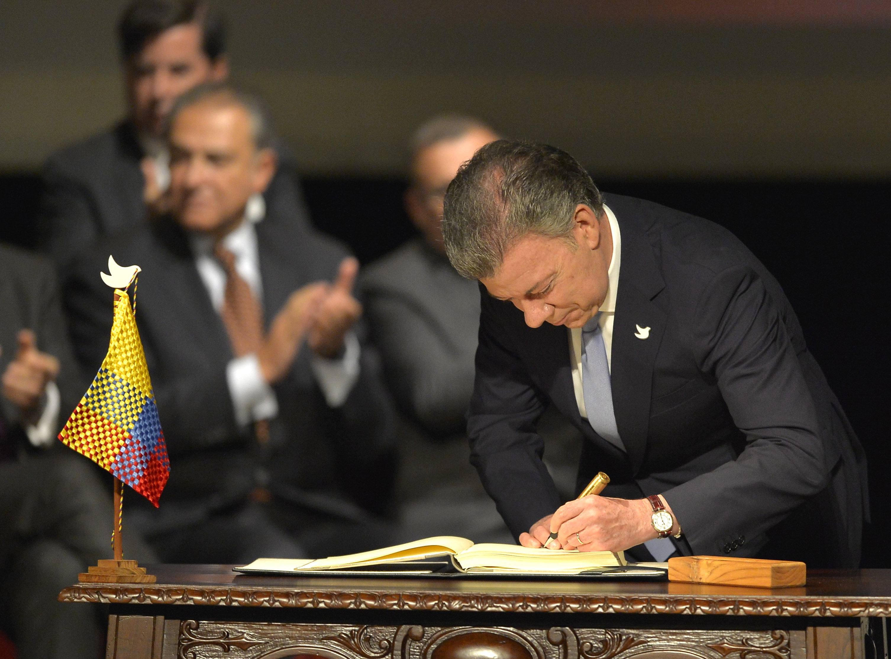 Colombian President Juan Manuel Santos (L) signs the historic peace agreement between the Colombian government and the Revolutionary Armed Forces of Colombia (FARC), at the Colon Theater in Bogota, Colombia, on November 24, 2016
