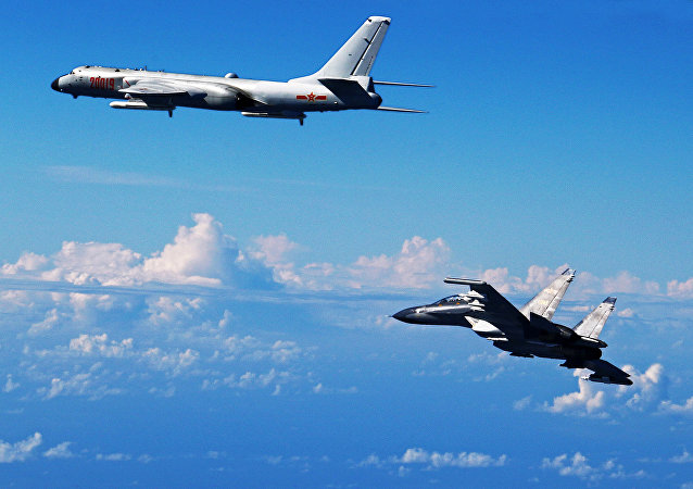 Chinese People's Liberation Army Air Force Su-30 fighter, right, flies along with a H-6K bomber as they take part in a drill.