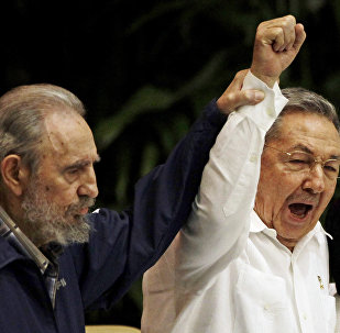 Fidel Castro, left, raises his brother's hand, Cuba's President Raul Castro, center, as they sing the anthem of international socialism during the 6th Communist Party Congress in Havana, Cuba (File)
