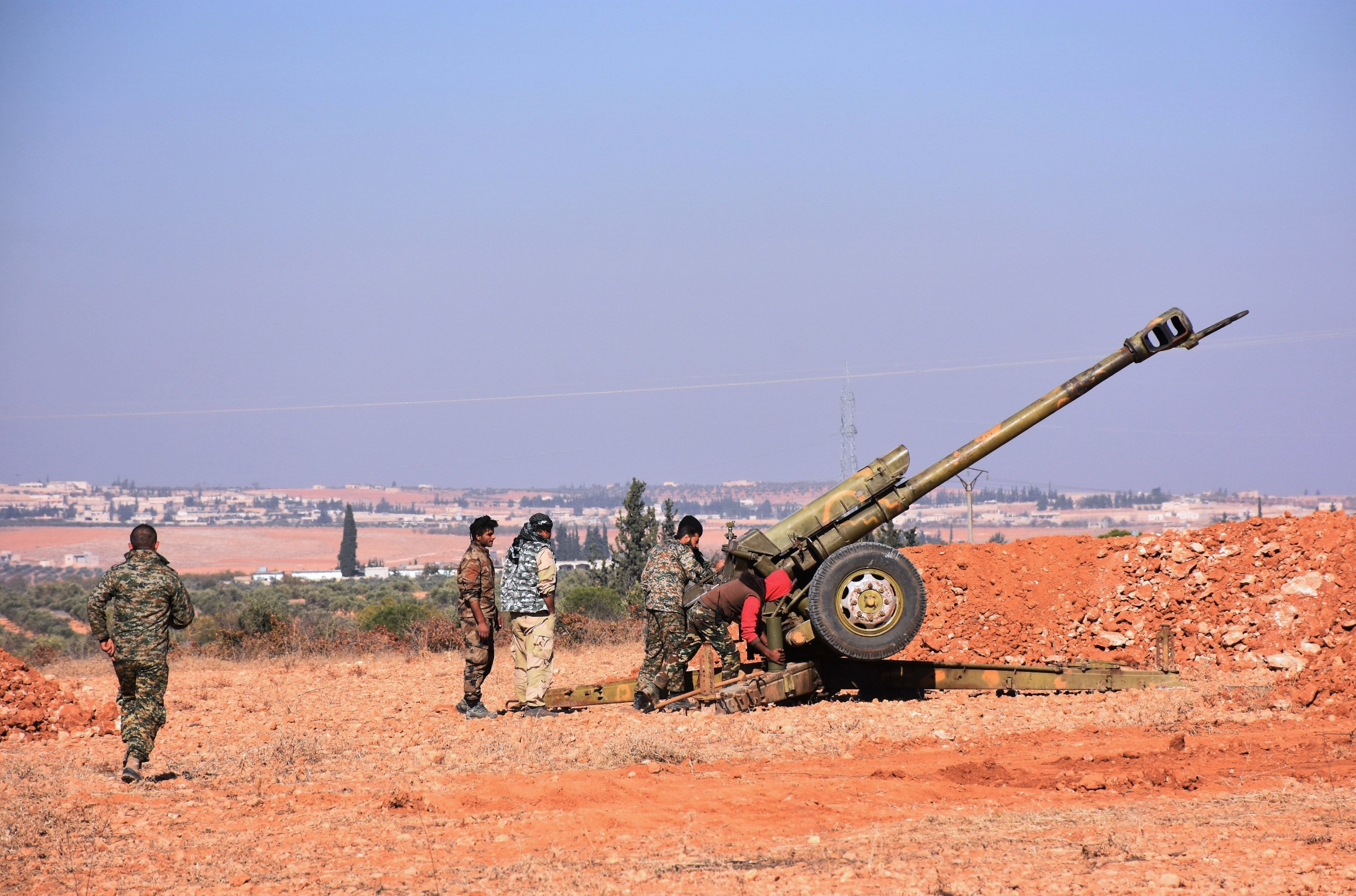 Syrian pro-government fighters fire a Russian 122mm howitzer gun as they advance in the recently recaptured village of Joubah during an offensive towards the area of Al-Bab in Aleppo province, on November 25, 2016
