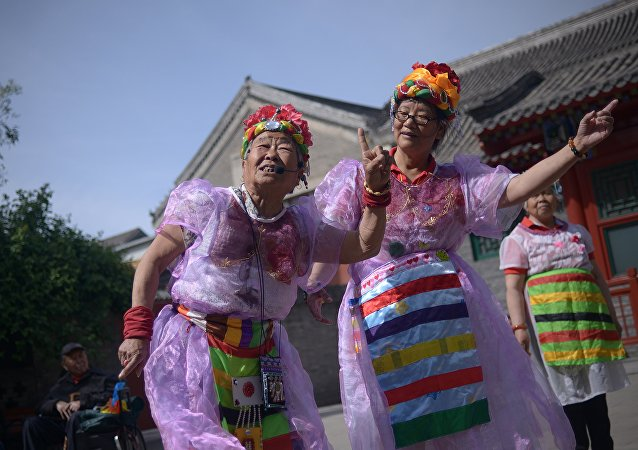 Two elderly women perform a dance at a park near the Forbidden City in Beijing