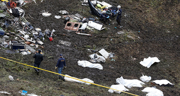 Rescue workers walk next to bodies from the wreckage of a plane that crashed into the Colombian jungle with the Brazilian soccer team Chapecoense onboard near Medellin, Colombia