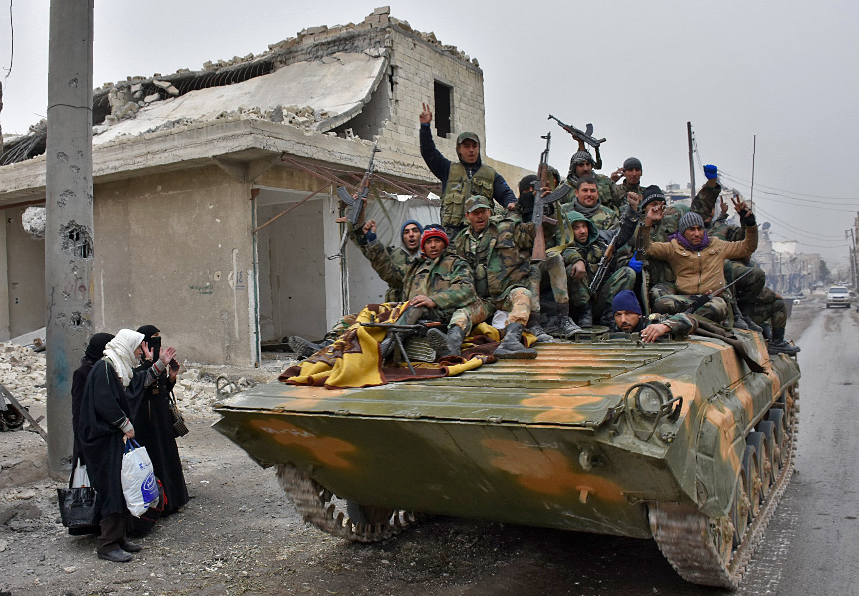 Syrian pro-government forces sit on a military vehicle driving past residents fleeing the eastern part of Aleppo and gathering in Masaken Hanano, a former rebel-held district which was retaken by the regime forces last week, on November 30, 2016.