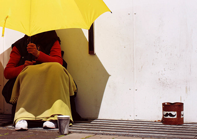 A beggar shields herself from the sun using a bright yellow umbrella, Malmo, Sweden