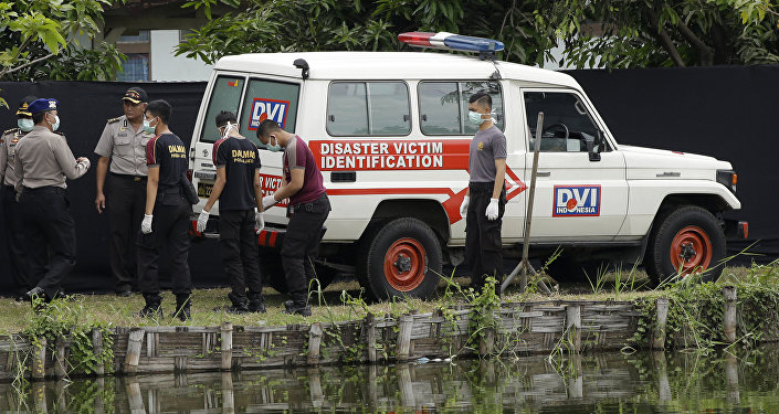 Indonesian police officers stand near an ambulance used to carry the bodies of the victims of a plane crash outside the morgue at the police hospital in Surabaya, East Java, Indonesia (File)