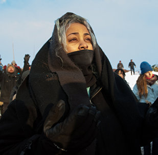 A woman watches the sunrise in Oceti Sakowin camp as water protectors continue to demonstrate against plans to pass the Dakota Access pipeline near the Standing Rock Indian Reservation, near Cannon Ball, North Dakota, U.S. December 3, 2016