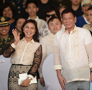 This file photo taken on July 1, 2016 shows Philippines' President Rodrigo Duterte (R) posing for photographs with Vice-President Leni Robredo after the military parade at the military headquarters in Manila